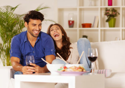 A man and woman sitting on the couch laughing and eating together.